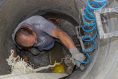 Worker inside a manhole, working in a manhole 2 — Stock Photo