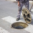 Utilities worker moves the manhole cover 2 — Stock Photo #34360763