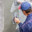 Stock Photo: Building worker spreading mortar on concrete wall 4