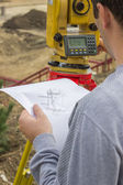 Land surveyor analyzing a cadastral and site plans — Stock Photo