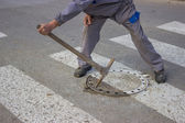 Utilities worker moves the manhole cover — Stock Photo