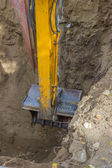 Excavator arm digging deep hole seeking cracked sewage pipe — Stok fotoğraf