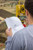 Land surveyor analyzing a cadastral and site plans on constructi — Stock Photo
