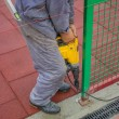 Construction worker uses a drill to make holes in a concrete 2 — Stock Photo #34759061