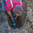 Stock Photo: Utility worker in trench repair broken pipe 2