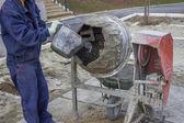Trabajador constructor poniendo agua en una mezcladora de cemento 2 — Foto de Stock