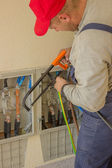 Electrician working with a chainsaw in the electrical cabinet — Stock Photo