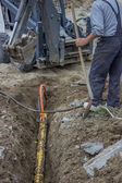 Mini excavator digging up a electrical cables from trench 4 — Stock Photo