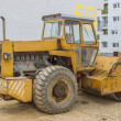 Stock Photo: Yellow road roller in the new residential area 3