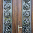 Beautiful wood door with metallic ornament — Stock Photo