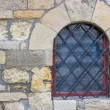Window with bars in the stone wall — Stock Photo