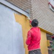 Builder workers plastering exterior wall — 图库照片