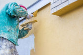 Builder worker plastering exterior wall — Stock Photo