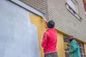 Builder workers plastering exterior wall — Stock Photo