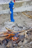 Fire hydrant and bonfire on construction site — Stock Photo