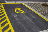 Handicap symbol painted on asphalt at parking space — Stock Photo