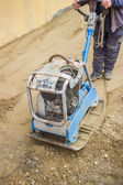 Worker with vibrating plate compactor machine — ストック写真