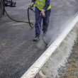 Stock Photo: Spraying bitumen emulsion with hand spray lance