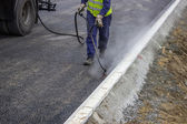 Spraying bitumen emulsion with the hand spray lance — Stock Photo