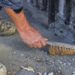 Foto Stock: Construction Worker with broom sweeping concrete