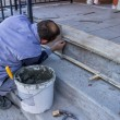 Foto Stock: Worker Install Ceramic Stairs Tile 2