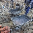 Stock Photo: Workers bringing mortar in wheelbarrow to work area
