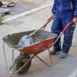 Builder worker pushing gravel wheelbarrow — Stock Photo