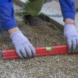Stock Photo: Worker checking horizontal level of ground for paving
