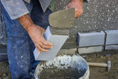 Builder holding a brick and with masonry trowel spreading and sh — Stock Photo