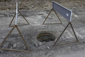 Road under construction, manhole cover missing — Stockfoto