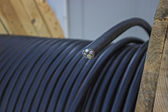 Roll of black industrial al cable with cross section — Stock Photo