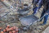 Workers bringing mortar in wheelbarrow to work area — Stock Photo