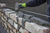 Build a brick wall, bricklaying spreading a bed joint — Stock Photo