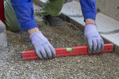 Worker checking horizontal level of ground for paving — Stock Photo