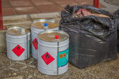 Cans of industrial chemical with flammable sign and bag of waste — Stock Photo