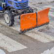 Tractor snowplow is cleaning the pedestrian crossing and sprinkl — Stock Photo #39670113