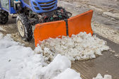 Tractor snowplow is cleaning the pedestrian crossing and sprinkl — Stockfoto