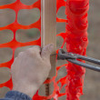 Stock Photo: Builder worker Installing Construction Safety Fence 4