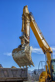 Excavator arm and dumper truck — Stock Photo