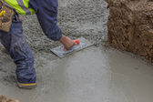 Construction worker using trowel to finish top of foundation — Stock Photo
