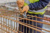 Workers hands using steel wire and pincers to secure rebar — Stock Photo