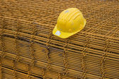 Stack of rebar grids with yellow helmet — Stock Photo