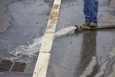 Man pumping away flood water — Stock Photo