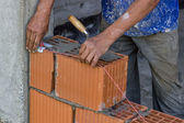 Building worker setting string line between clay block — Stock Photo