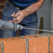 Construction worker uses drill to make holes in concrete 2 — Stock Photo #49748805