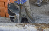 Builder worker wetting concrete with bucket of water 2 — Stock Photo