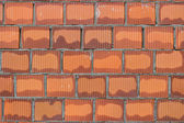 Orange hollow clay block in fresh mortar, wall background — Stock Photo