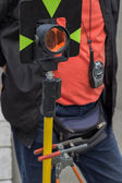 Theodolite prism with survey worker in background — Stock Photo