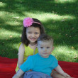 Baby boy and his sister in the park. — Stock Photo #27296003
