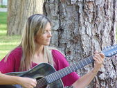 Beautiful young woman play the guitar out of doors. — Stock Photo